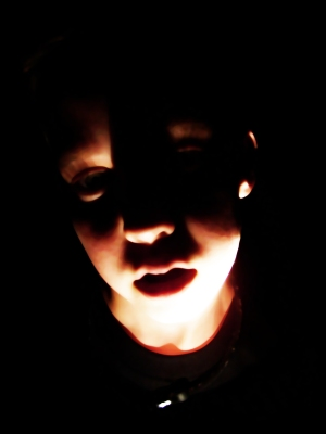 Boy holds flashlight up to his face in the dark