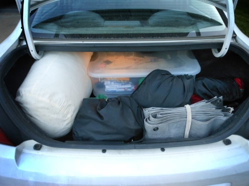 A car trunk fully loaded with camping gear