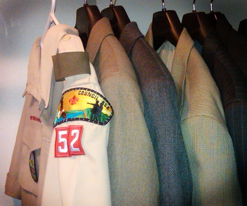 A Boy Scouts Leader shirt hangs in a closet alongside business attire