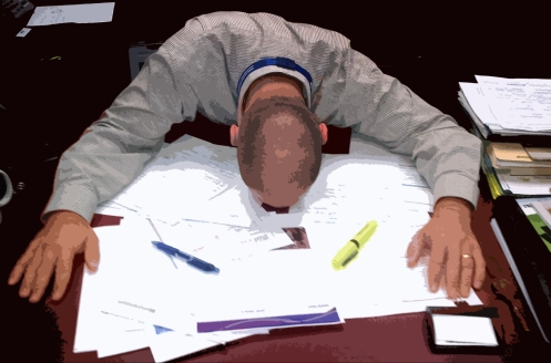 Man collapsed at a desk of paperwork