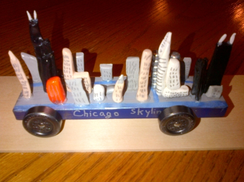 Pinewood Derby car designed to look like the Chicago skyline.  Dad broke this one and had to help repair it -- and son.