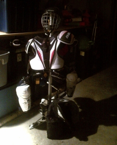 Hockey gear drying rack in a dark garage