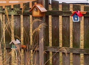 Three birdhouses on a fence